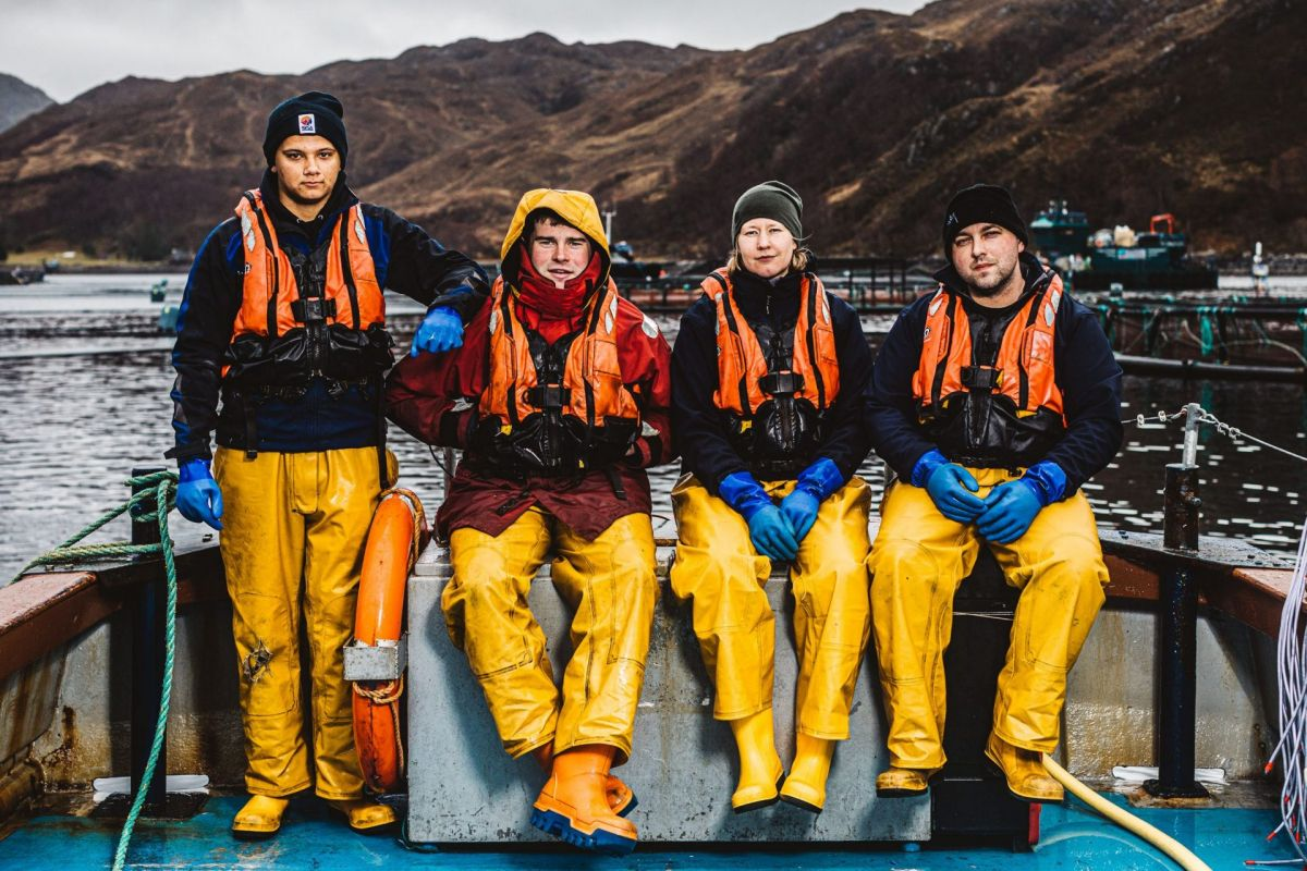 crew of salmon workers looking to camera