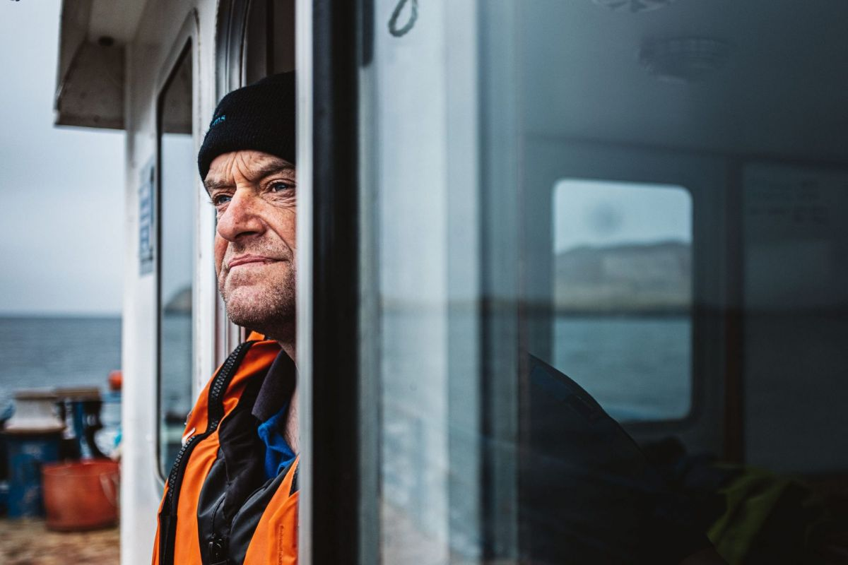 man with rugged face looks out to sea