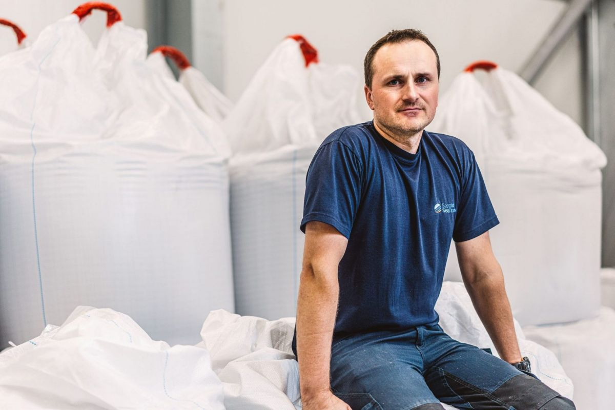man sitting with bulk bags of feed