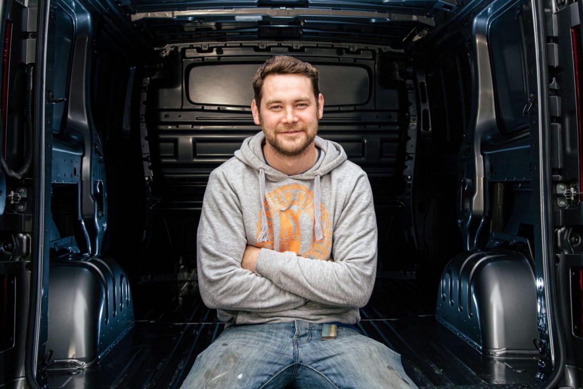 man sitting in back of a van
