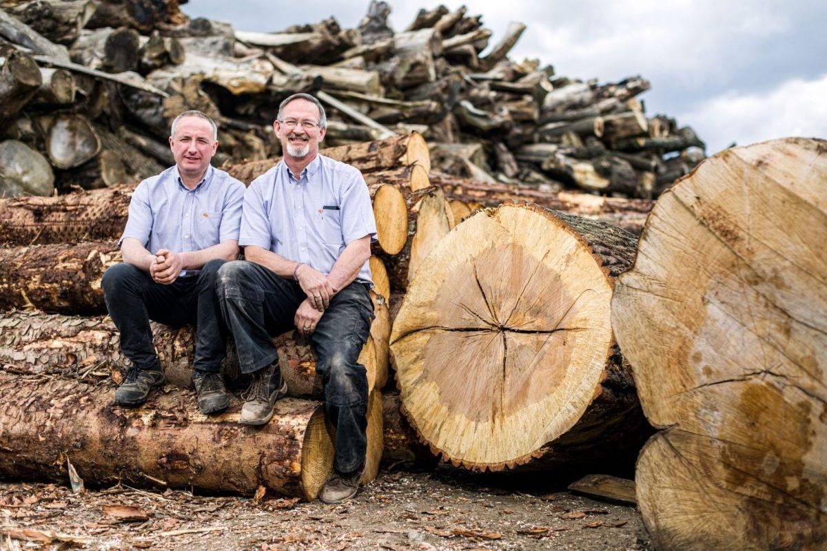 two men sitting in a lumber yard