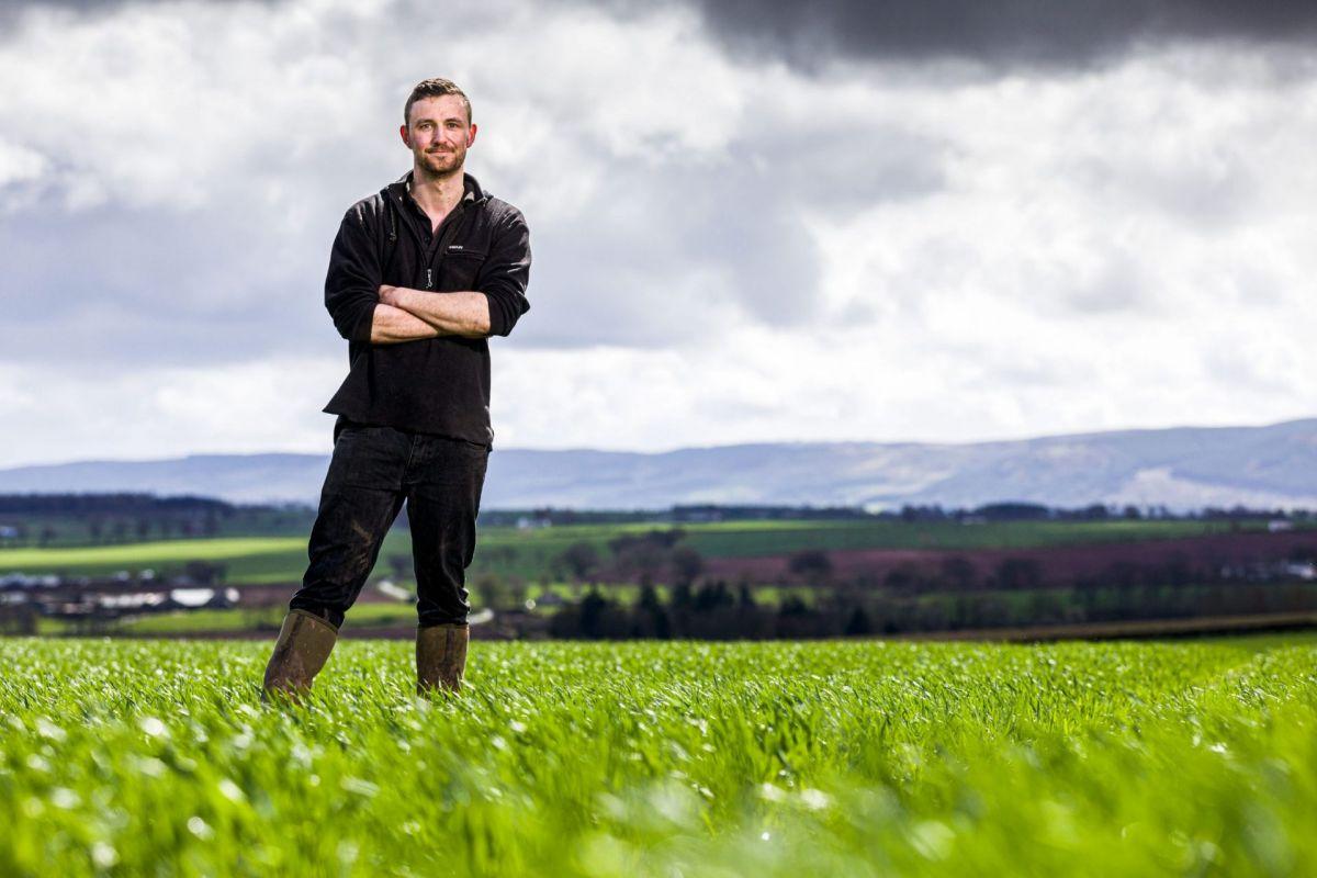 young male arable farmer in crop field