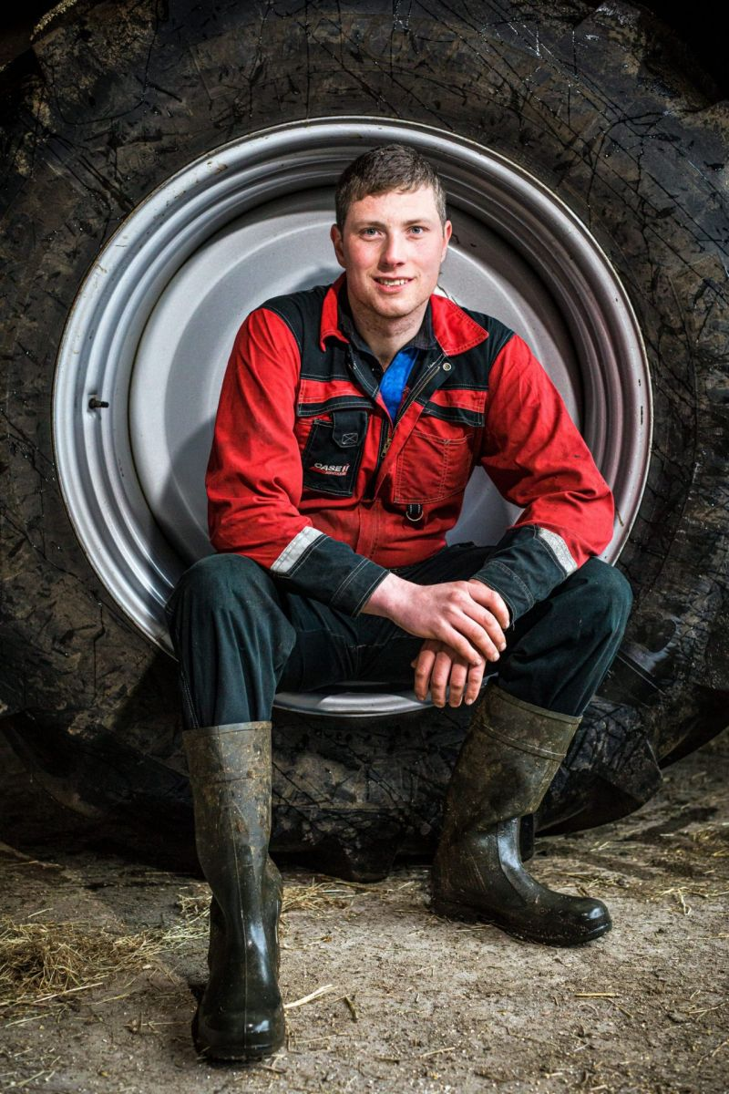 young male farmer sitting in tractor wheel