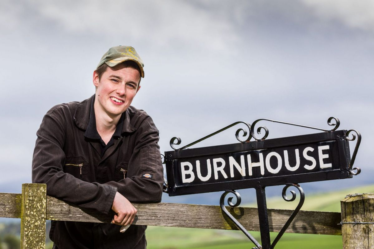 Young male farmer with farm sign